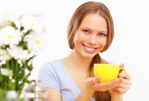Молодая мама блондинка пьет чай