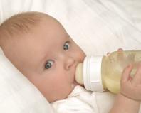 Ребенок кушает молочную смесь из бутылочки с соской