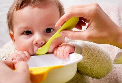 Ребенка кормят с ложечки