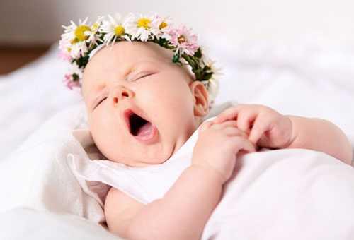 Новорожденная девочка зевает