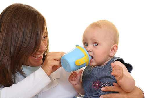 Мама дает ребенку жидкость из детской поилки