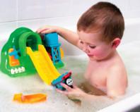 Ребенок играет с миниатюрной водной горкой