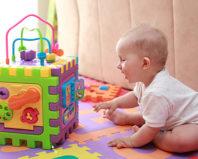 Малыш играет с развивающей игрушкой