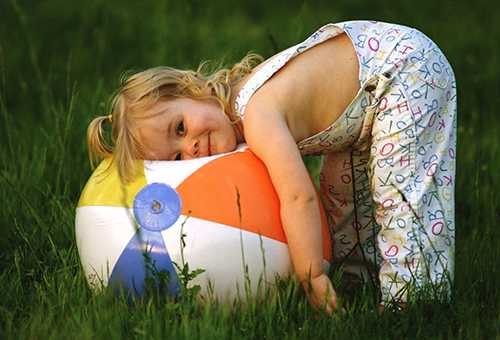 Девочка с большим мячом на свежем воздухе
