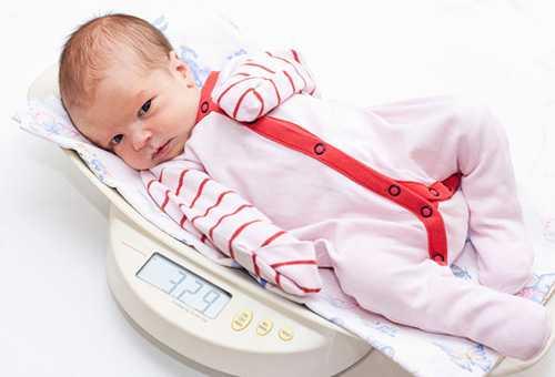 Новорожденный ребенок на весах