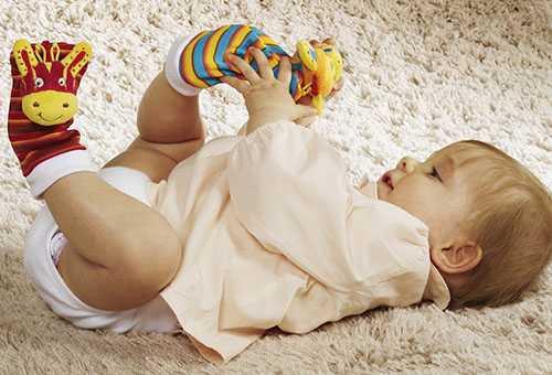 Ребенок играет с яркими носочками