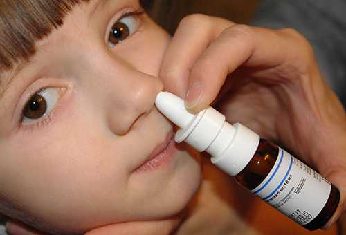 Ребенку закапывают спрей от насморка