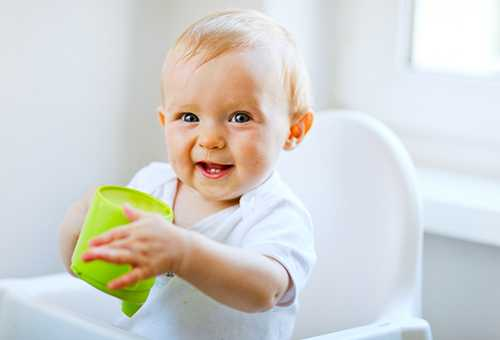 Радостный маляш держит детскую кружку