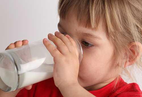 Ребенок пьет молоко из стакана