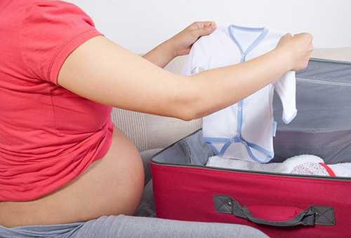 Будущая мама рассматривает детскую распашонку