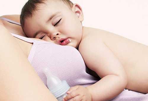 Сытый малыш спит у мамы на груди с молочной смесью в руке