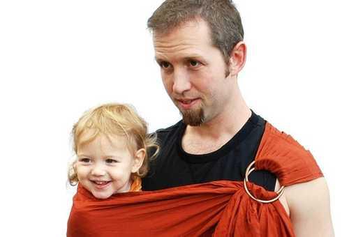 Молодой папа с ребенком в слинге