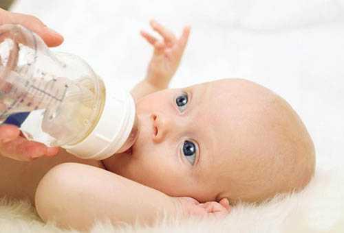 Ребенок пьет из бутылочки с соской