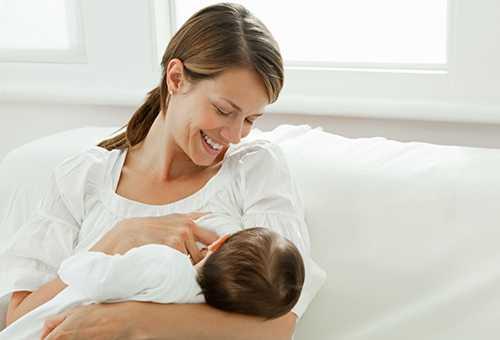 Мама держит новорожденного в горизонтальном положении