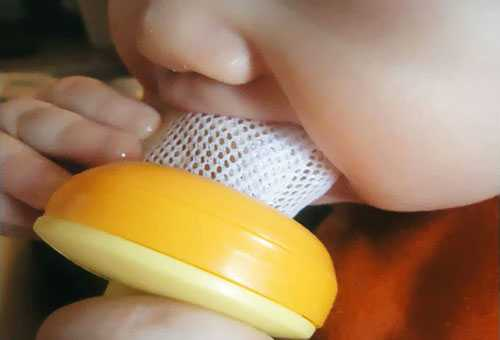 Ребенок кушает из сеточки для прикорма