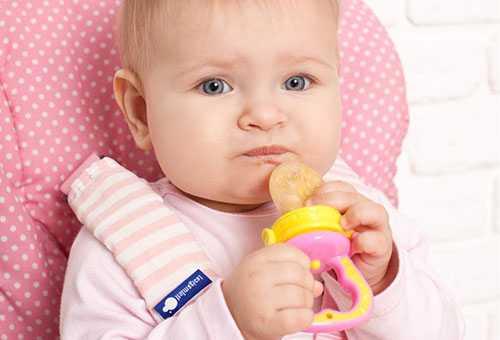 Ребенок кушает прикорм с помощью ниблера