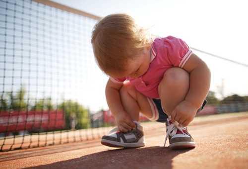 Трехлетний ребенок пытается сам завязать шнурки