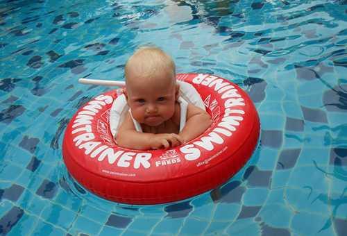 Младенец в плавательном круге в бассейне