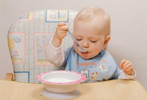 Ребенок кушает, сидя в детской стульчике