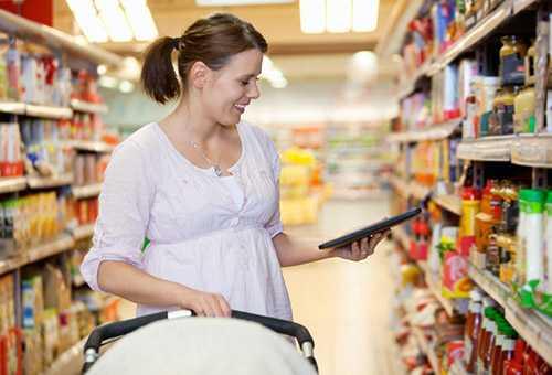Мама с грудничком выбирает продукты в магазине