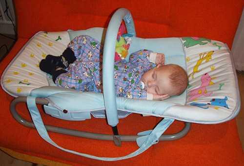 Грудничок спит в шезлонге для новорожденных
