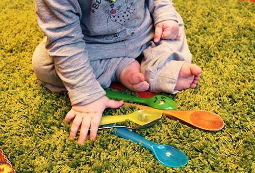 Ребенок играет разноцветными ложками