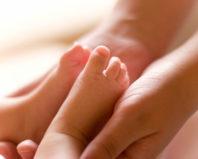Ножки ребенка в маминых руках