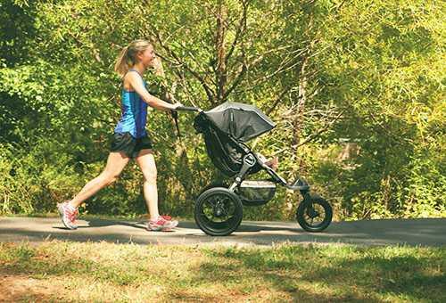 Спортивная молодая мама на прогулке с новорожденным