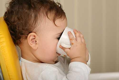 Ребенок учится пить из кружки