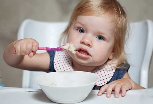 Маленькая девочка ест картофельное пюре