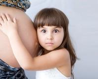 Девочка обнимает мамин животик