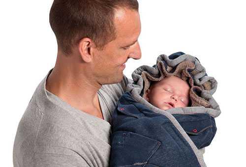 Папа держит малыша, одетого в конверт для новорожденных