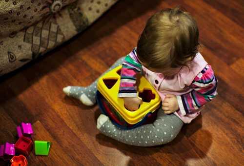 Малыш играет с геометрическими фигурами