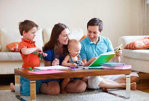 Родители с детьми изучают развивающую книжку