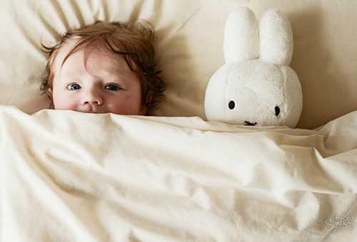 Малыш под одеялом с плюшевым зайцем