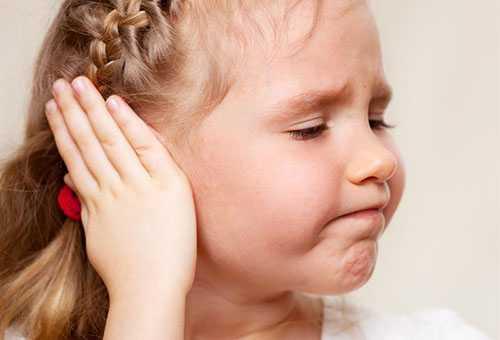 Девочка закрывает ладошкой ухо