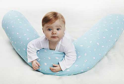Маленький ребенок держит подушку-валик