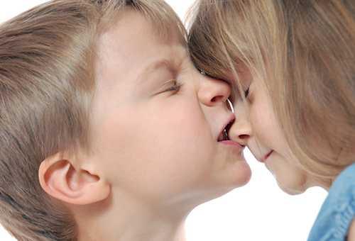 Мальчик кусает девочку за нос