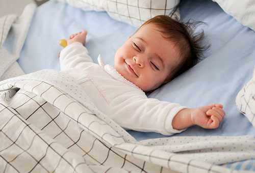 Ребенок улыбается во сне