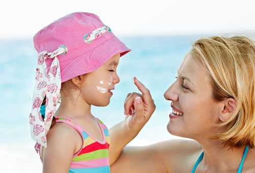Мама мажет лицо девочки солнцезащитным кремом