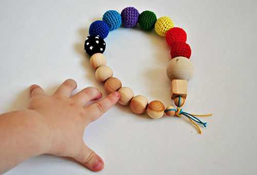 Ребенок тянется к самодельной игрушке в виде бус