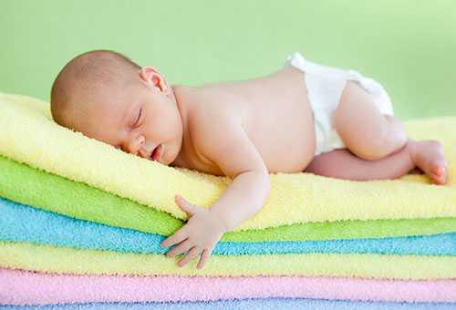 Ребенок спит на стопке полотенец