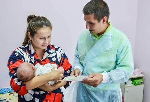 Молодая мама с новорожденным и врач