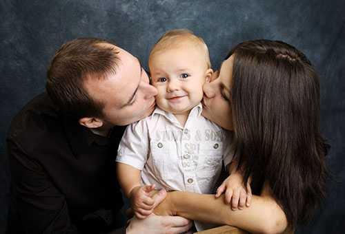 Родители целуют годовалого малыша