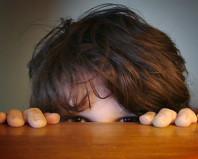 Ребенок прячется за столом