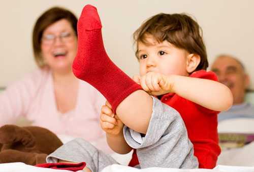 Ребенок надевает носок самостоятельно