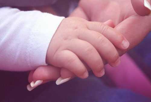 Ручка младенца в маминой ладони