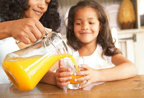 Мама наливает дочери сок