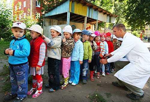 Дети стоят друг за другом в детском саду