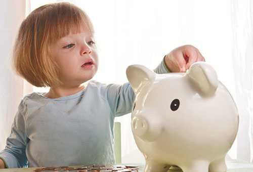 Девочка бросает монетку в копилку
